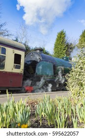 Vintage steam train pushes old carriage by a platform on a sunny Spring day
