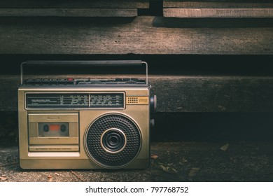 Vintage stereo in the 90s put on cement floor at roadside with wood background. The light goes down on the stereo.