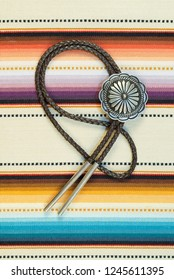 Vintage Sterling Silver Bolo Tie with Concho and Silver Tips on colorful southwestern hand woven fabric.