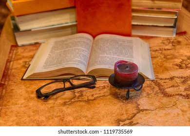 Vintage still life: a book, glasses and candle against the background of stacks of books and an ancient world map
