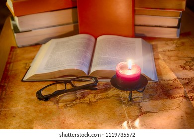 Vintage still life: a book, glasses and a burning candle against the background of stacks of books and an ancient world map
