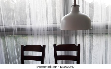 Vintage still life. Chairs in front of white curtain, under the lampshade.