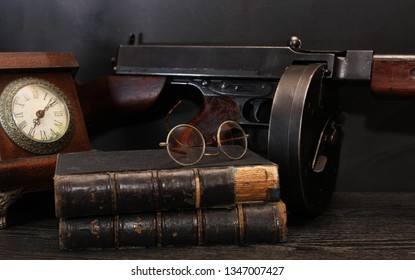 Vintage still life with clock and old USA submachine gun on dark background