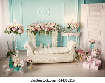 Vintage still life decor with bouquet of fresh flowers.  Peony and roses in vases and candles on luxury retro interior background. Still-life decoration concept in french boudoir style. Film grain