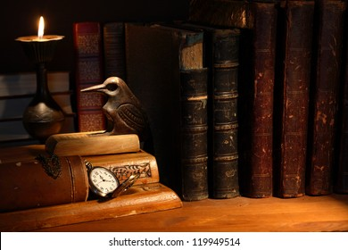 Vintage still life with desk set and ancient books near candle