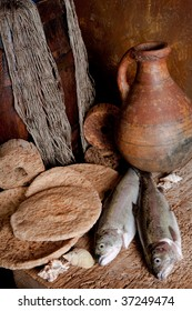 Vintage still life of fresh fish with loaves of bread and an antique wine jar