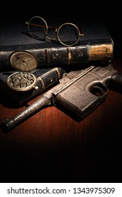 Vintage still life with handgun and spectacles near old books
