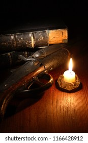 Vintage still life with hunting shotgun near candle and old books