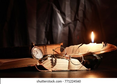 Vintage still life with lighting candle near old things