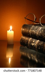 Vintage still life with lighting candle near old book