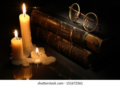 Vintage still life with lighting candles near books on dark background