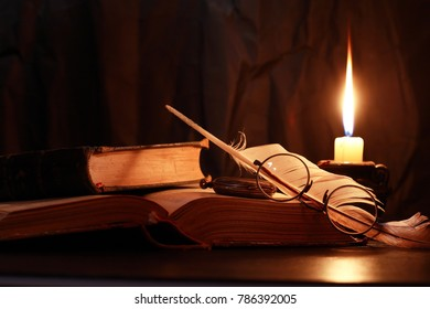 Vintage still life with lighting candles near books and old things
