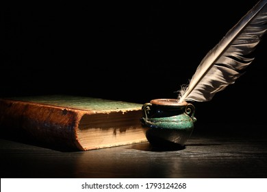 Vintage still life with old book and quill pen on dark background