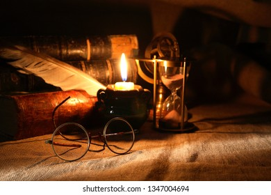 Vintage still life with old glasses against lighting candle and books