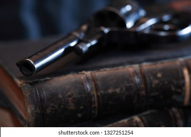 Vintage still life. Old handgun on book against dark background