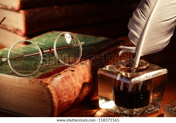 Vintage still life. Old spectacles on book near glass inkwell with quill pen