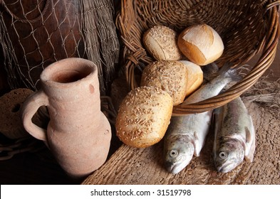 Vintage still life of an old wine jug with bread loaves and fresh fish