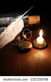 Vintage still life with quill pen and spectacles on old books near lighting candle
