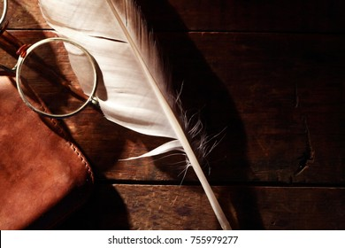 Vintage still life. Quill pen and old spectacles on wooden background