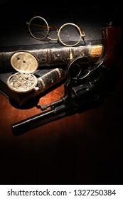 Vintage still life with revolver and spectacles near old books