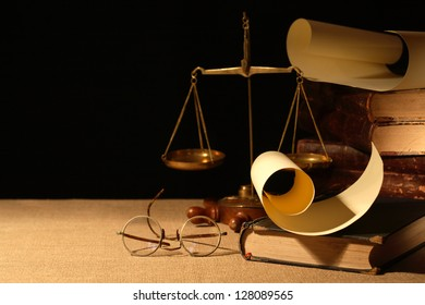 Vintage still life with spectacles near brass weight scale and books on dark background