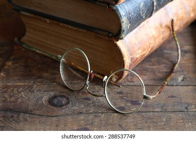 Vintage still life with stack of old books near spectacles