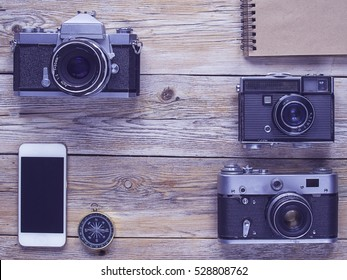 Vintage still-life with old retro cameras on a wooden table. Photo accessories and photography tools.