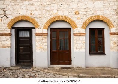 Vintage stone building facade with dark wood doors and windows