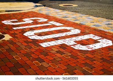 Vintage stop sign on city red brick floor.