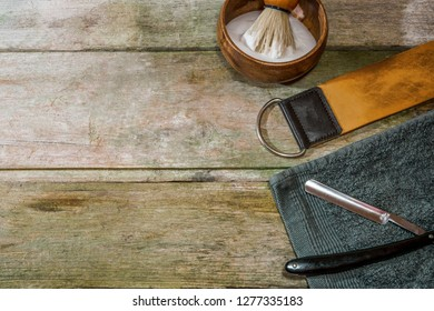 Vintage straight razor, leather strop and shaving brush. Old-school wet shaving in rustic wooden table, with copy space.