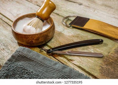 Vintage straight razor, leather strop and shaving brush in bowl. Wet shaving supplies in wooden table, with copy space.