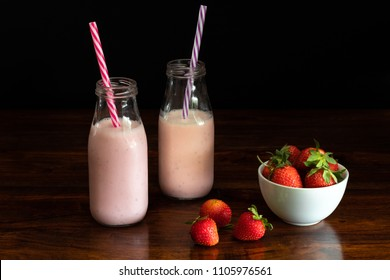 Vintage strawberry milkshakes on black background