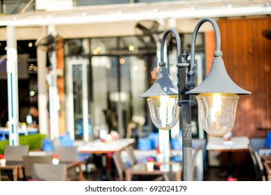 The vintage street lamp (lantern) shine near the outdoor restaurant for background or texture. - Shutterstock ID 692024179