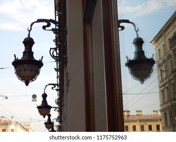 Vintage street lamp on the wall of the house and its reflection in the window