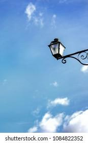 vintage street light against blue sky bottom view