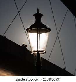 Vintage streetlamp lit by the sun shining through from the back with the silhouette of part of a modern steel bridge in the back (low depth of field)