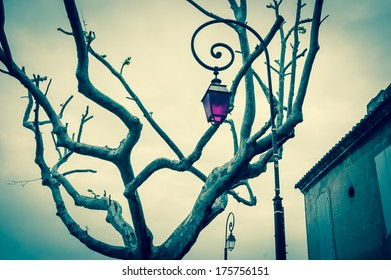Vintage streetlight with magenta color glass, tree, old house and the second streetlight with normal glass at backgrounds. (Arles, Provence, France). Concepts of unique, different and standing out.