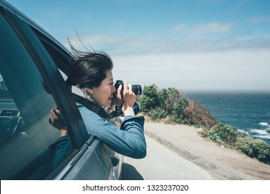 vintage style of asian female tourist taking photo with professional camera during car road trip on the famous 17 mile drive highway. Coastline along the 17 Mile Drive in Pebble Beach of Monterey