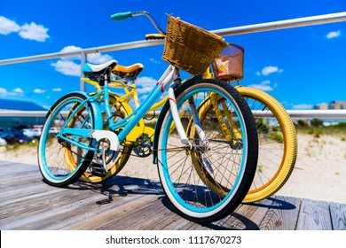 Vintage Style Bicycles Teal and Yellow on Ocean City New Jersey Boardwalk with Beautiful Blue Sky with some Clouds Vivid Colors