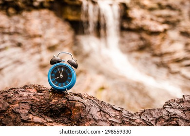 Vintage style - Blue alarm clock on tree texture on waterfall.