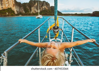 Vintage style child portrait. Happy baby girl on board of sailing yacht have fun discovering islands in tropical sea on summer coastal cruise. Travel adventure, yachting with kids on family vacation.