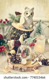 vintage style christmas decoration with small child figurine in glass dome and owl standing on tree stump