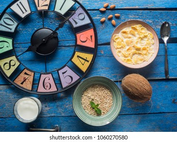 vintage style clock, bowl of cornflakes with milk, oatmeal, coconut, almonds, a glass of milk and flowers on blue painted plank table