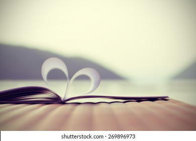 vintage style, close up heart shape from paper book with lake and mountain (blur background)
