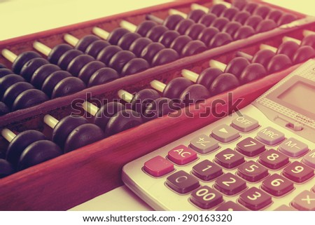 Vintage style - Close up of a wooden abacus beads and calculator. Selective focus, shallow depth of field. Wooden abacus on table wood texture background.