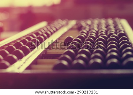 Vintage style - Close up of a wooden abacus beads. Selective focus, shallow depth of field. Wooden abacus on table wood texture background.
