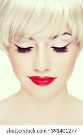 Vintage style close-up portrait of young beautiful smiling woman with red lips and winged eyes