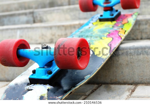 Vintage Style Colorful Skateboard with Red Wheels on a Street Stairs