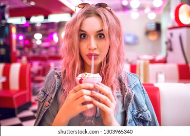 Vintage style cute portrait of happy surprises edited woman drinking tasty milkshake, pastel soft colors, unusual pink hairs, American neon cafe, trendy outfit.