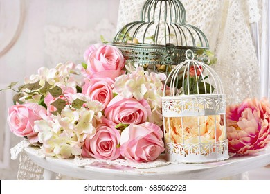 vintage style decoration with flowers in old metal bird cages and bunch of pink roses on the chair